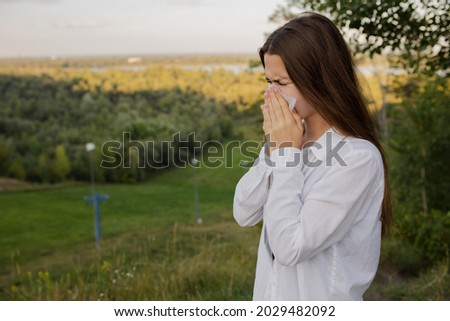 A girl with a cold blinks into a handkerchief in the street. The girl sneezes in nature. Bloom allergy. A girl in a white shirt blinks into a handkerchief. Foto stock ©