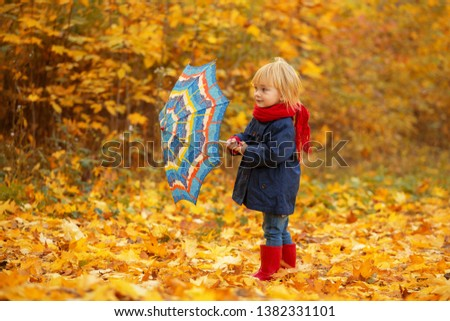 A girl with a colorful umbrella is walking around an autumn park. #1382331101