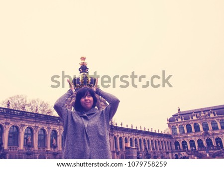 A girl with a crown on her head in Zwinger, Dresden. Forced perspective photography.  #1079758259