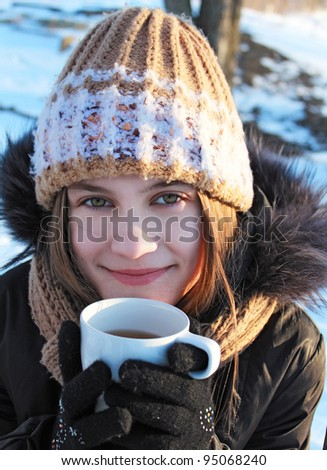 A girl with a cup of drink outdoors