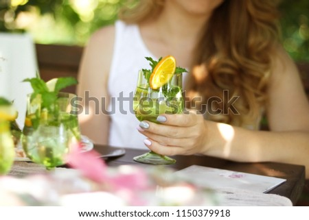 A girl with a glass sits in a cafe. A glass of lemonade in the hands of a girl. #1150379918