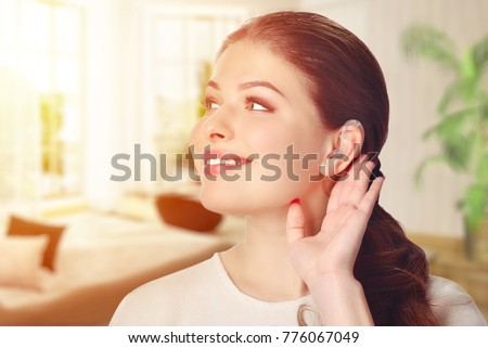 A girl with a hearing aid. The girl assumes hearing aid. In the room. Happy girl that hears well again