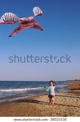 a girl with a kite running along the sea