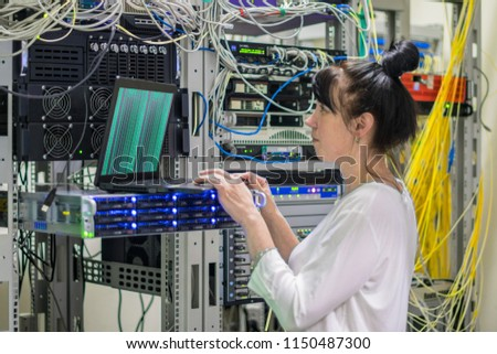 A girl with a laptop works in the server room. The woman downloads the software on a powerful networked Internet equipment. The system administrator is in the datacenter #1150487300