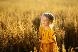 A girl with a long Russian braid in a yellow dress is standing in a wheat field. Image with selective focus, toning and noise effect.