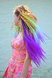 A girl with a long wavy hair painted in rainbow colors. Tunic hair kanekalon