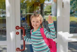A girl with a pink satchel opens the school door. Children go out to study after vacation and the coronavirus epidemic. The new school year