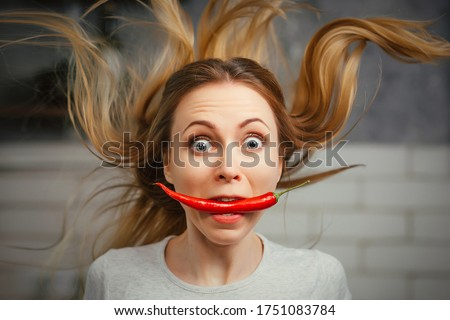 A girl with a red hot pepper in her teeth. Chili for cooking. The spicy seasoning is very stinging in the mouth. My hair stood on end. Bite the pepper and get burned. Emotional woman.