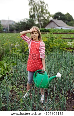 A girl with a water can in a kitchen-garden