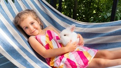 A girl with a white bunny lies on a hammock in the summer on a sunny day. White fluffy decorative rabbit in the arms of a little girl. Hare as a pet. The child holds his little rabbit in his hands.