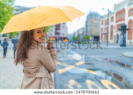 A girl with a yellow umbrella is hiding from the rain. Beautiful woman with umbrella on a rainy day. Attractive young woman carrying umbrella and smiling while standing on the street
