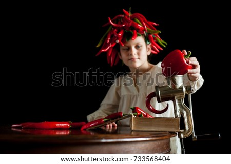 A girl with an extravagant haircut made from red chili peppers puts a large pepper into a meat grinder. Selective Focus #733568404