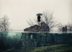 A girl with an umbrella standing on the ruins of a flooded building in the rain. Surreal landscape with lonely woman in black dress and old house