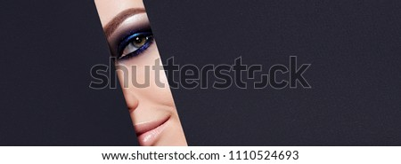A girl with beautiful green bright eyes with blue shining shadows, beige lipstick and expressive eyebrows looks into the hole of colored paper. #1110524693