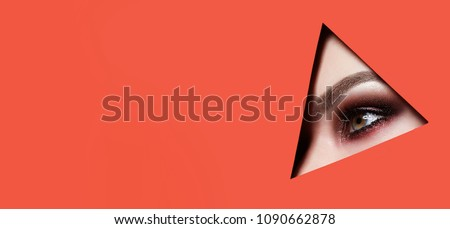 A girl with beautiful green bright eyes with brown shadows and expressive eyebrows looks into the hole of colored paper.Fashion, beauty, make-up, cosmetics, beauty salon, style, personal care.