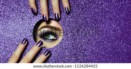 A girl with beautiful long fingers and lilac nails touches the edge of her open eye in a round hole of lilac shiny paper. A lilac eye shadow.Fashion, beauty, make-up, cosmetics, beauty salon, style.