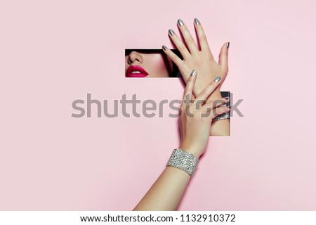 A girl with beautiful long fingers and silver nail polish with pink lipstick on the lips with metallic effect closes her eyes in a rectangular hole of pink paper of paper.  #1132910372