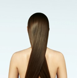 A girl with beautiful silky long blond hair turned her back to the audience on a white background.