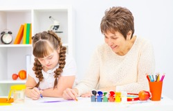 A girl with down syndrome is studying at home with her mother. Girl and mother sitting at the table draw a picture at home.