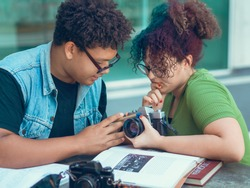 A girl with glasses with red and blue curly hair and a boy in a denim jacket analyze an old analog camera, underneath they have photography books.