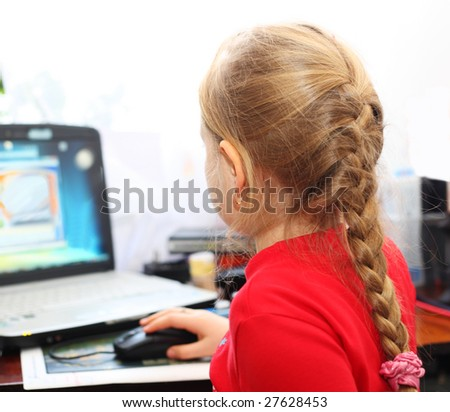 A girl with gold earrings playing computer games.