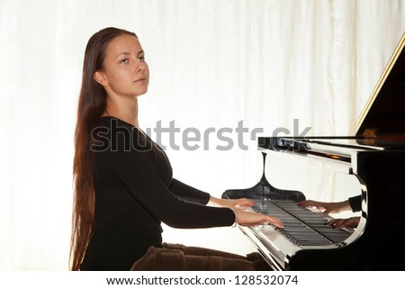 A girl with her hair playing the piano in a concert hall