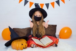 A girl with long blond hair in a hat and in a witch costume for Halloween with a witch's book, in a black mask, shows a cool class. Protection in quarantine.