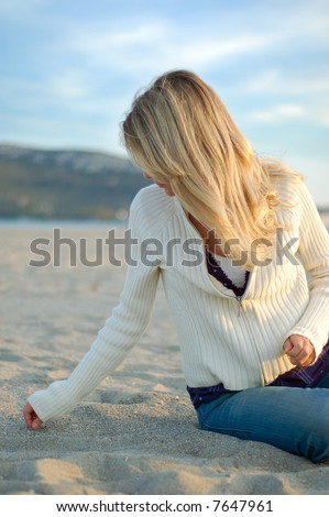 stock photo : a girl with long blonde hair is searching some seashells on a