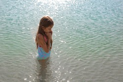A girl with long hair in a blue bathing suit with pink sea stars stands in the clear blue sea water and shivers. It's too cold to swim. Lifestyle contest.