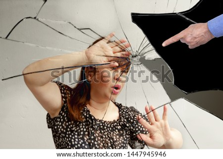 a girl with long hair is pushed away by her hands from the pointing gesture of a man's hand, reflected in a broken mirror, concept of violence, mobbing #1447945946