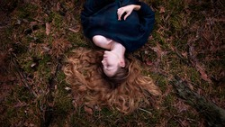 A girl with long hair lies on a green moss in the forest