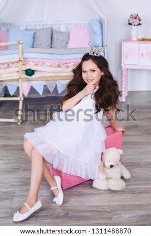 A girl with lush hair in a white dress is sitting on a pink suitcase with a teddy beige bear, holding her hand at the chin.