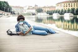 A girl with phone sitting near the river