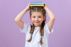 A girl with pigtails in a white T-shirt and books in her hands on an isolated background.