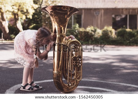 A girl with pigtails tries to play tuba