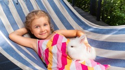A girl with positive emotions lies on a hammock and holds a white decorative rabbit in her hands. A beautiful fluffy bunny in the arms of a happy child. The pet breed is a dwarf rabbit.