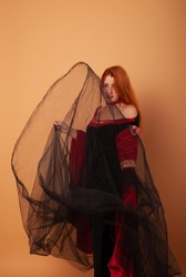 A girl with red hair in a dress of a vampire countess or a witch with a black veil who flies in the air. Halloween