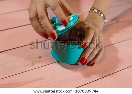 a girl with red nails opens a wedding bonbonniere (candy-box) #1078839944