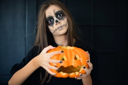 A girl with scary makeup and a halloween pumpkin, halloween make up concept