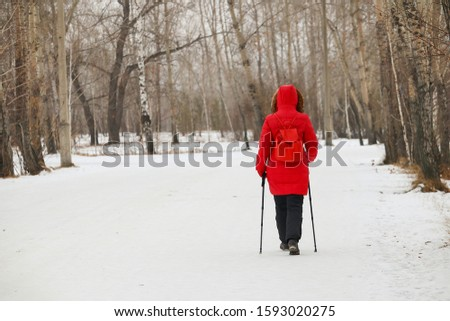 A girl with sticks for Nordic walking, in a red down jacket walks through the forest, view from the back