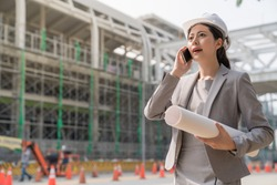 A girl woman engineer speaking to someone on the cellphone . She wears a white hard cap standing aside the building site .