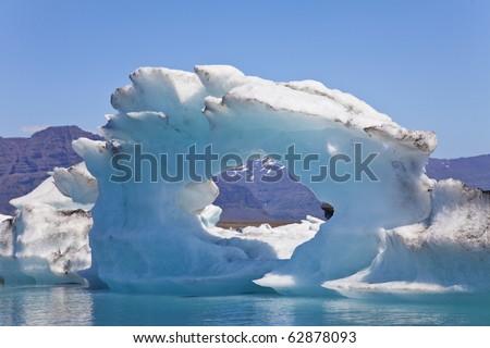 A glacial iceberg with a hole through its center floating on the Iceberg Lagoon, Jokulsarlon, Iceland
