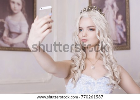 A glamorous girl, a blond woman in a crown, makes a selfie. Spoiled girl, a daughter of an oligarchy. Photograph on an expensive smartphone, narcissist. Princess on the background of the picture.