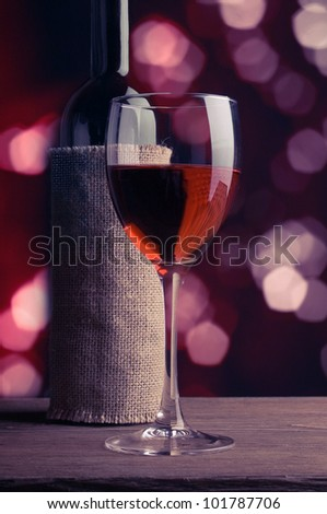 A glass and a bottle of red wine.