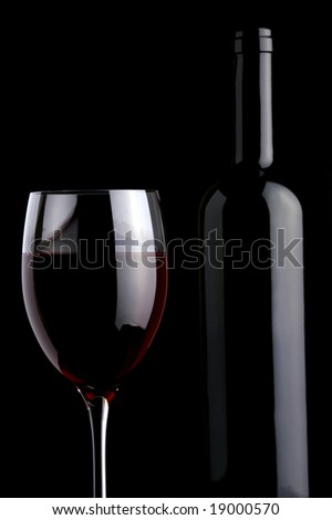 a glass and a bottle of red wine on  a black background