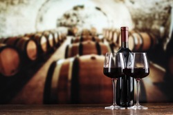 a glass and a bottle of wine on the background of barrels in the cellar