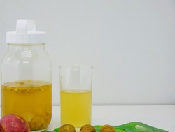 A glass bottle and glass filled with sucrose solution for preparation of homemade kambucha probiotic drink with tropical fruits such as passionfruits and rambutans. Healthy drink for digestive system.