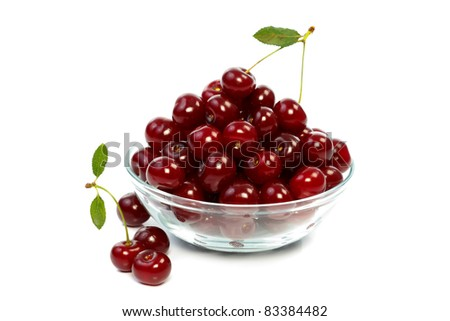 A glass bowl full with sweet cherries