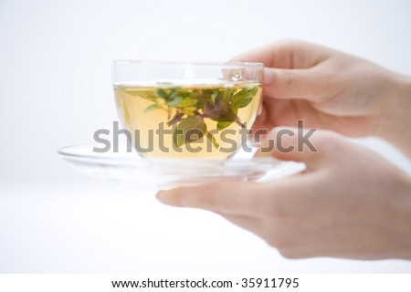 A glass cup of herb tea with woman's hands