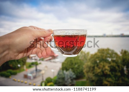 A glass cup with tea in hand against a background of urban morning scenery. Motivating picture for a cheerful and good day. Wishing good morning. Energy charge.